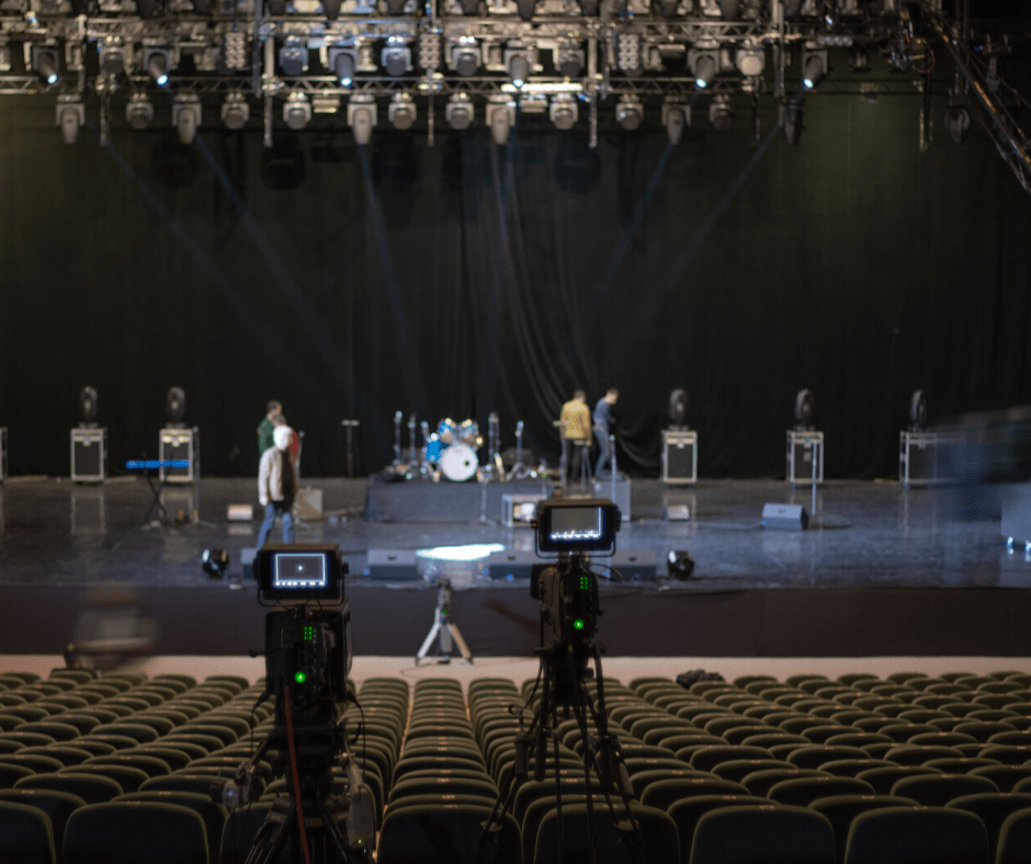 Two cameras pointed at a stage while a band sets up